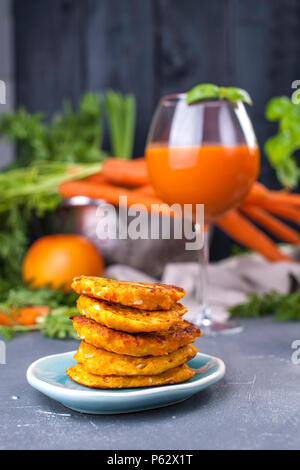 Juice from fresh carrots and grapefruit in a glass and fragrant pancakes for breakfast. vitamin drink for a healthy diet. Vitamins in food. Copy space - Stock Photo