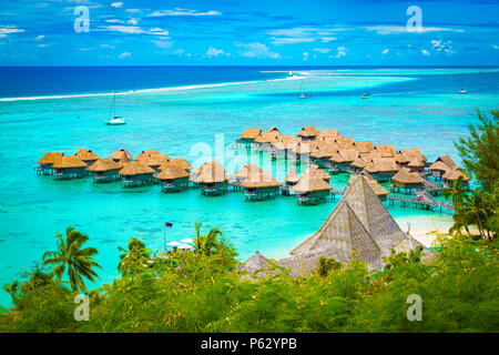 Aerial view of overwater bungalow luxury resort in turquoise lagoon water of Moorea, French Polynesia. - Stock Photo