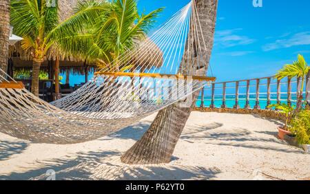 Hammock on tropical beach. - Stock Photo