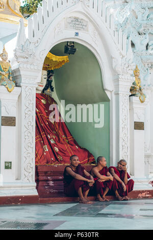 Yangon, Myanmar - FEB 19th 2014: Monks are sitting in front of temple at Shwedagon Pagoda - Stock Photo