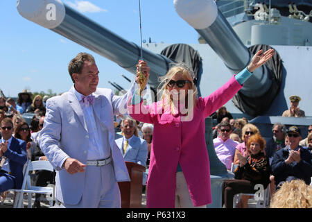 Anna Kooiman, Queen of the Azalea Festival, rejoices after cutting the ceremonial cake with the naval officer's sword, kick-starting the celebration of the 75th anniversary of the USS North Carolina (BB-52) Battleship's commissioning in Wilmington, N.C., April 9, 2016. Marines and sailors from 2nd Tank Battalion and other 2nd Marine Division units volunteered to work with museum staff and members of Living History to give real-life experiences to guests partaking in the festivity. (U.S. Marine Corps photo by LCpl. Miranda Faughn/Released) - Stock Photo