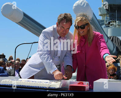 The ceremony announcer and Anna Kooiman, Queen of the Azalea Festival, cuts a ceremonial cake with the naval officer's sword to kick-start the 75th anniversary celebration of the commissioning of the USS North Carolina (BB-52) Battleship in Wilmington, N.C., April 9, 2016.  Miss North Carolina, Kate Peacock, and the rest of the Azalea Festival court also attended the ceremony. (U.S. Marine Corps photo by LCpl. Miranda Faughn/Released) - Stock Photo
