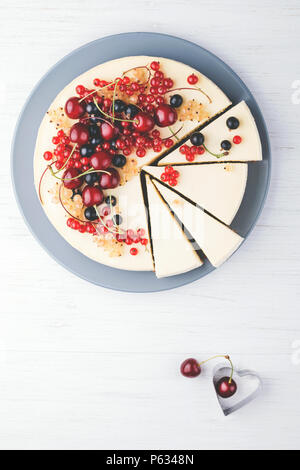 Homemade cheese cake New York with berries on white wooden table. Top view. Red currant, black currant and cherry. - Stock Photo