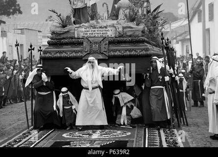 PRIESTS and PENITENTS with ANDA (wooden float sculpted in 1650) during GOOD FRIDAY PROCESSION - ANTIGUA, GUATEMALA - Stock Photo