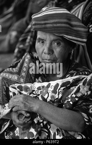 MAYAN WOMAN wearing traditional brocade HUIPILS in MARKETPLACE - CHICHICASTENANGO, GAUTAMALA - Stock Photo