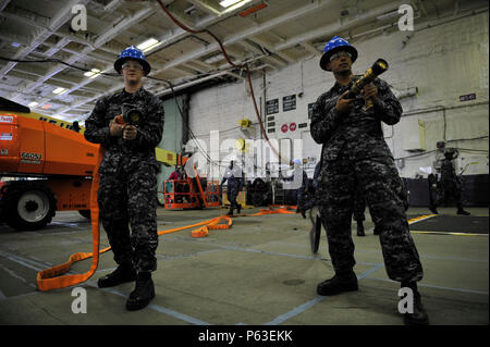 NEWPORT NEWS, Va. (Apr 19, 2016) -- Sailors assigned to Pre-Commissioning Unit Gerald R. Ford (CVN 78) perform firefighting drills in the ship's hangar bay. Ford is the first of a new class of aircraft carriers currently under construction by Huntington Ingalls Industries Newport News Shipbuilding. (U.S. Navy photo by Mass Communication Specialist Seaman Apprentice Connor Loessin/Released) - Stock Photo