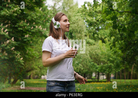 Young pregnant girl listens to music on headphones in a city park. She is holding a cell phone in her T-shirt and jeans. Online radio - Stock Photo