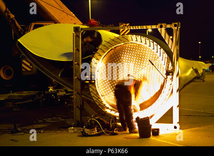 Long exposure shot of a wind turbine blade being assembled by workers in preparation for assembly on site. Worksop United Kingdom. December 2008. - Stock Photo