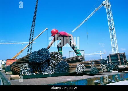 Unloading steel reinforcement bundle from lorry by crane on a construction site at the Rion-Antirion bridge site in Greece - Stock Photo