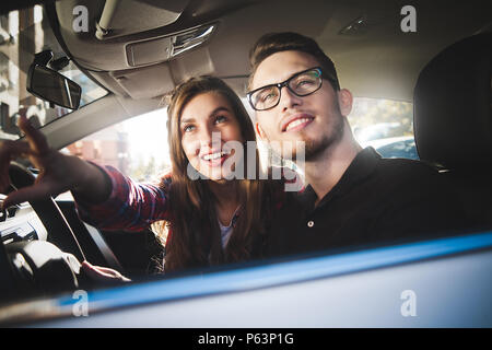 Enjoying travel. Beautiful young couple sitting on the front passenger seats and smiling while handsome man driving a car. - Stock Photo