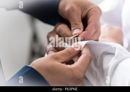 A groom putting on cuff-links as he gets dressed in formal wear. Groom's suit - Stock Photo