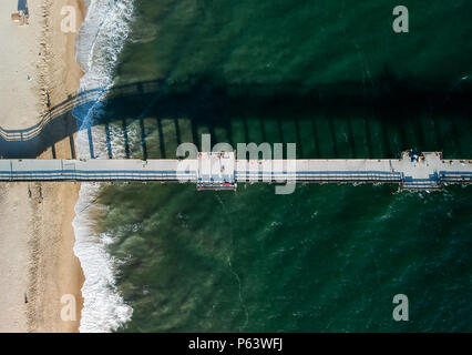 An aerial shot at 330 feet/100 meters looking down on a Southern California pier located on a small peninsula. White foam from crashing waves and vibr - Stock Photo