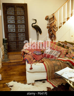 White sofa piled with Indian cushions and throw in townhouse living room with carved wooden Indian door - Stock Photo