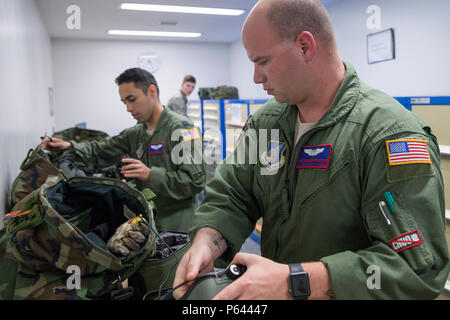 Tech. Sgt. Christopher Rector, right, 459th Airlift Squadron UH-1N special missions aviator evaluator, and Capt. Jonathan Bonilla, left, 459th AS UH-1N pilot, prepare their night vision goggles at Yokota Air Base, Japan, April 25, 2016. The 459 AS regularly conducts training missions to keep their skills proficient. (U.S. Air Force photo by Yasuo Osakabe/Released) - Stock Photo