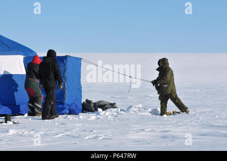 A Canadian Ranger, a Canadian engineer and an Airman with the New York Air National Guard's 109th Airlift Wing set up camp at Little Cornwallis Island, Nunavut, Canada, on April 6, 2016, in support of Canada's annual Operation Nunalivut. A group of eight Airmen with the 109th AW prepared a ski-way for LC-130 operations while training four Canadian enginners on how to construct the ski-way. Two Canadia Rangers were also on-hand to provide perdator support. Nearly 50 Airmen and two LC-130s from the 109th were part of the exercise which also had operations in Resolute Bay, Canada, and Thule Air B - Stock Photo