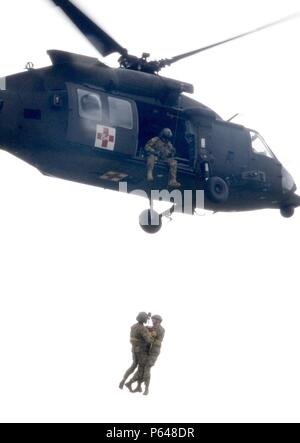 NORTH FORT HOOD, Texas--Courtesy of the United States Army Reserves 7th Battalion, 158th Aviation Regiment, First Army commanding general, Lt. Gen. Michael S. Tucker, learned hoist operations up close and personal here, April 20. Tucker, bottom right, dangling from the line, took part in hoist training conducted by the 7-158th while training for an upcoming deployment in support of contingency operations. - Stock Photo