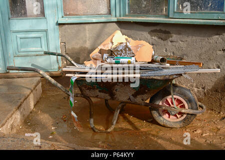 A builder's wheelbarrow full of rubbish outside of a house under renovation, UK - Stock Photo