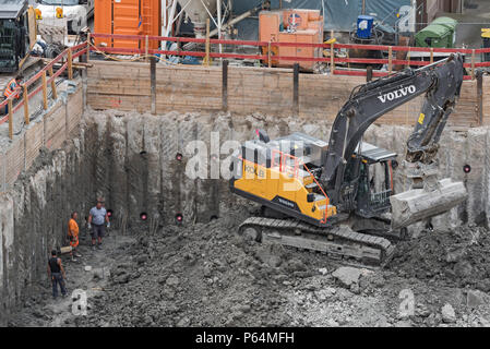 wheel loader lifting the cellar on a construction site - Stock Photo
