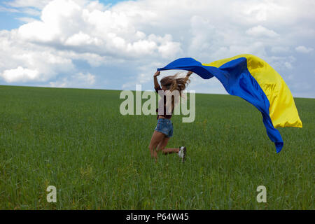 young beautiful ukrainian girl with an excellent figure in short jeans shorts holds a national Ukrainian yellow blue flag developing in the wind again - Stock Photo