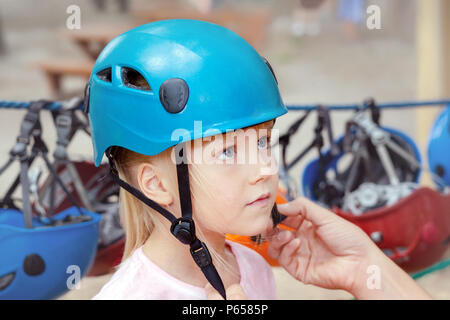 Little cute blond girl putting on helmet. Father helping daughter to put on helmet before extreme sport recreation. Parent take care of children health and safety during outdoor summer activities - Stock Photo