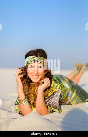 Young woman wearing green beach robe lying on white sand. - Stock Photo