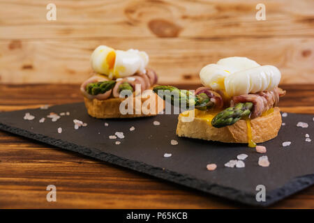 Grilled toast with asparagus in bacon and poached egg on wooden background - Stock Photo