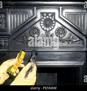 Cleaning a cast iron Victorian fireplace - Stock Photo