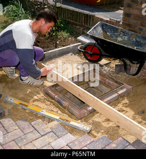 Laying paving stones around a manhole in a front garden. - Stock Photo