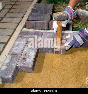 Laying paving stones in a front garden. - Stock Photo
