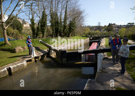 boaters working lock with narrowboat in number 12 lock as it floods with boat rising Kennet and Avon Canal Bath England UK - Stock Photo