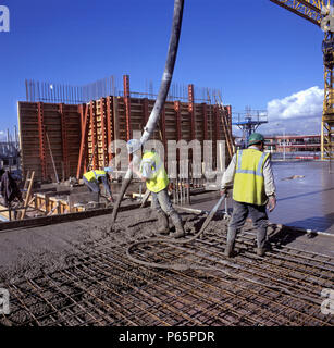Placing and spreading pumped in situ concrete to reinforced slab. - Stock Photo