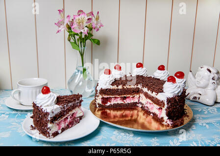 Chocolate cake with cream and cherry on the serving table. - Stock Photo