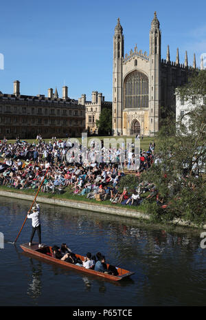 A Punt makes it's way along the river in front of Kings College Chapel at the University of Cambridge. - Stock Photo