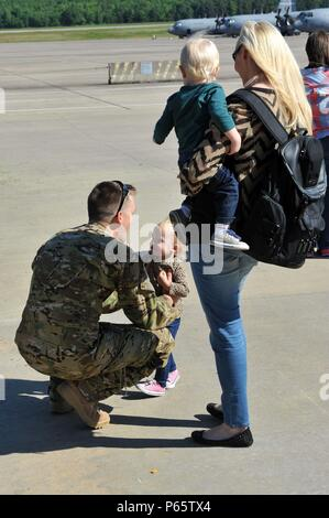 U.S. Air Force Staff Sgt. Patrick McCartney, 61st Airlift Squadron logistics office, says his final goodbyes to his twins Maddison and Conner and his wife Amanda prior to leaving for a routine deployment to Southeast Asia April 5, 2016, from Little Rock Air Force Base, Ark. Airmen of the 61st Airlift Squadron, 19th Aircraft Maintenance Squadron and 19th Maintenance Squadron along with a fleet of C-130J's left to support allied forces in the region.  (U.S. Air Force photo by Staff Sgt. Jeremy McGuffin) - Stock Photo