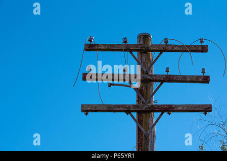 An old and dilapidated, disconnected electricity power pole in country NSW, Australia with dangling wire - Stock Photo
