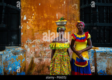 Afro-Colombian girls, dressed in the traditional 'palenquera' costume, pose for a picture in walled city of Cartagena, Colombia. - Stock Photo