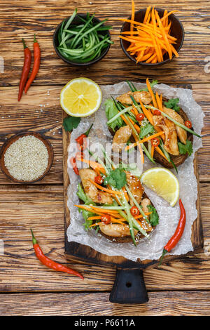 Asian sandwich with fried chicken and fresh vegetables-carrots, cucumber, chili pepper, cilantro and sesame. Selective focus. Top view - Stock Photo