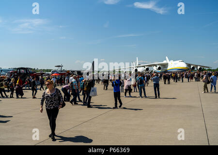 Visitors to the exhibition on the airfield. In the background, strategic airlift cargo aircraft Antonov An-225 Mriya. - Stock Photo