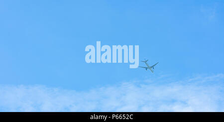 Airplane on blue sky and white clouds. Commercial airline flying on blue sky. Travel flight for vacation. Aviation transport. - Stock Photo