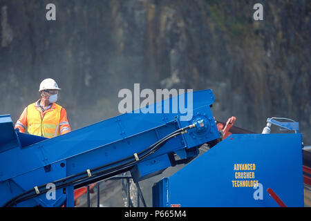 Worker in protective clothing working on crusher at quarry, United Kingdom. - Stock Photo