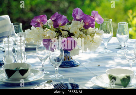 Still-Life of purple ipomea and white summer flowers in vase on table with wineglasses - Stock Photo