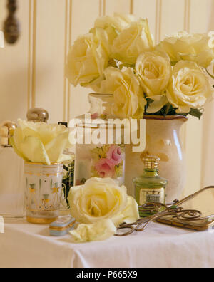 Still-Life of vase of cream roses with rose patterned jar and vintage perfume bottle - Stock Photo