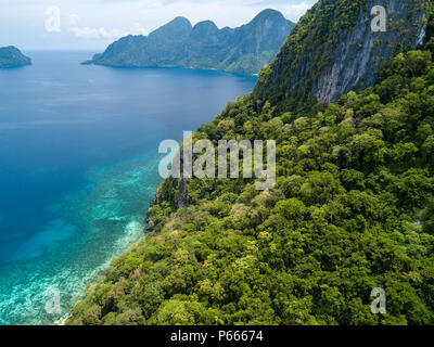 Aerial drone view of beautiful tropical coral reef with jungle and tall cliffs - Stock Photo