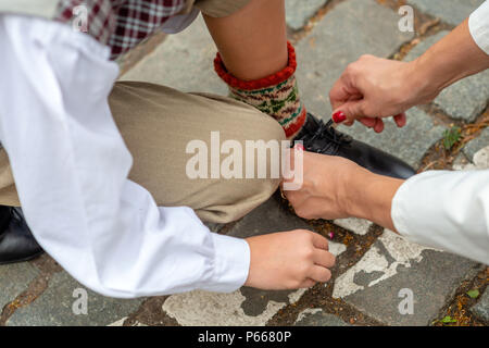Mother is helping his son to tie his shoes before the concert. - Stock Photo