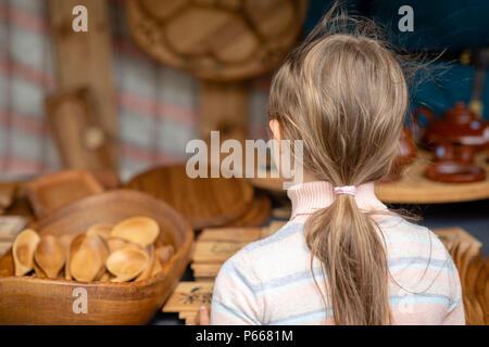 The girl is looking at wood products on the market. View from the back. - Stock Photo
