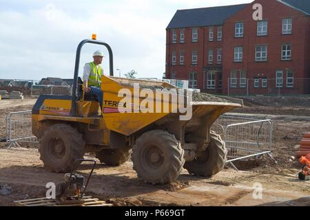 Workman driving a dumper truck with crushed stone. - Stock Photo