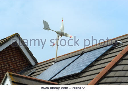 Micro Wind Turbine, Solar Voltaic and Evacuated solar tubes on roof of house in Ferndown Dorset England. - Stock Photo