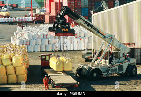 Forklift Loading Sacks Of Mineral on Truck at the port of Mejillones in Chile - Stock Photo