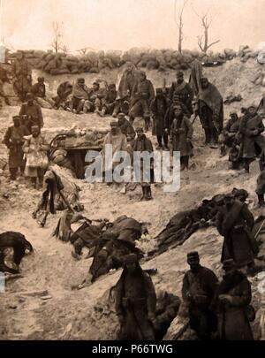 French soldiers takeover a German trench position as enemy casualties lie covered with coats during world war one 1916 - Stock Photo