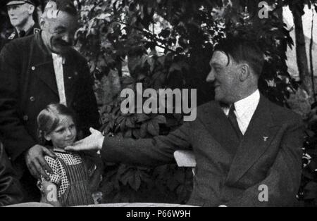 Adolf Hitler 1889-1945. German politician and the leader of the Nazi Party greets a young girl - Stock Photo